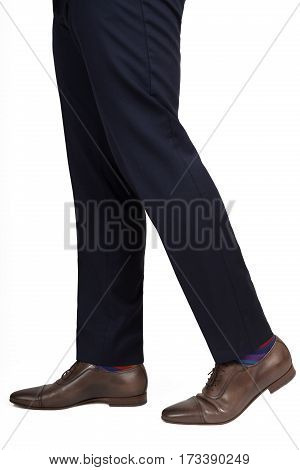 Close-up of man shoes and trousers in walking position isolated on white background