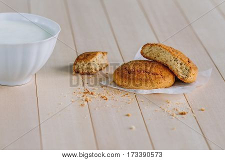 Dessert. Fresh delicious cookies on a wooden table. Near the cookie is white cup with yogurt. Crumbs on the table. Sweet Home a cozy family home morning.