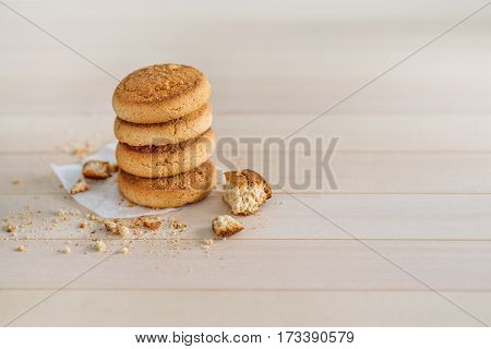 A stack of fresh delicious cookies on a wooden background. Crumbs on the table. Sweet Home a cozy family home morning.