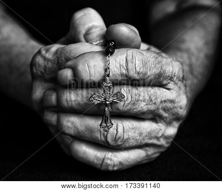 Rosary in old closed hands together. Black and white fotography