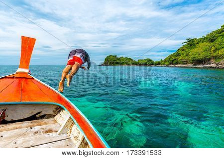 Young man jumping into the sea from longtail boat