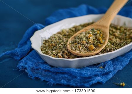 Dried chamomile or camomile flowers to make medicinal infusions on a blue background