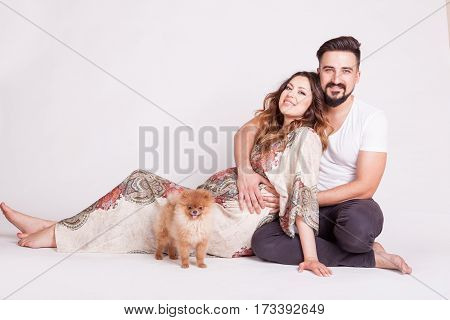 Pregnant Wife Next To Husband And Their Small Dog