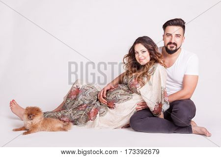 Pregnant Woman Next To Man And Their Dog