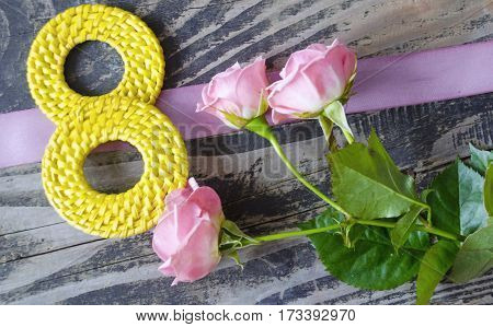 8 March symbol and roses. Figure of eight made of handmade buttons with roses on wooden background. Happy woman's day design. Can be used as a greeting card for international Woman's Day on 8 March.