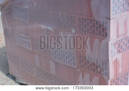 Close up on Stacks of packed in film bricks outdoor. Brick building materials protected from rain on the construction site.
