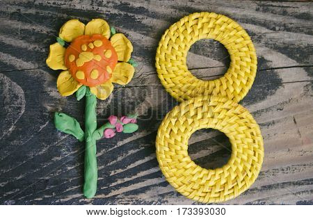 8 March symbol and handmade plasticine flower on wooden background. Happy woman's day design. Can be used as a decorative greeting card or postcard for international Woman's Day on 8 March.