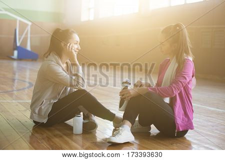 Two Smiling Women Relaxing After Class In The Gym