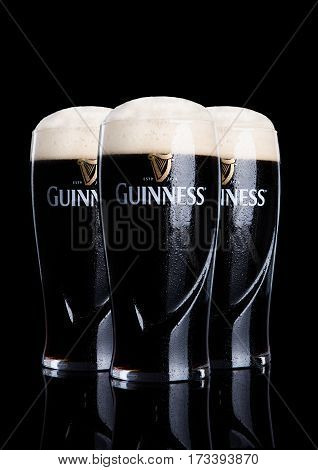 LONDON UK - FEBRUARY 26 2017: Glasses of Guinness original beer on black background. Guinness beer has been produced since 1759 in Dublin Ireland.