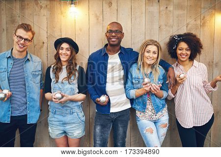 Group of five young good looking people in casual wear standing at wooden wall posing to camera holding steel petanque balls in hands