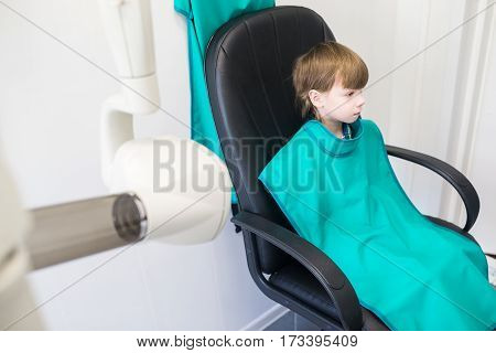 child sits in the office of the radiologist and is waiting for the procedure