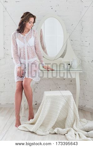 Sensual portrait of beautiful woman on the morning of the bride in a white Studio in the erotic lingerie.