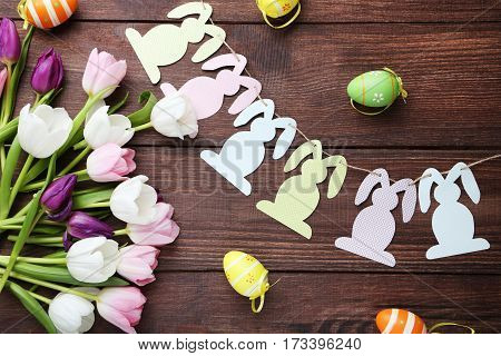 Bouquet Of Tulips With Handmade Easter Rabbits And Eggs On Brown Wooden Table
