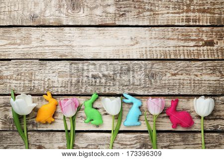 Handmade Easter Rabbits With Tulips On Grey Wooden Table