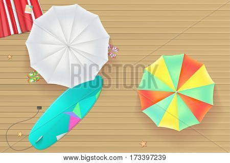 Background for summer holidays. Colored sun umbrellas, surfboard, flip-flops and a beach Mat on the wooden background from light brown straps. Tropical seashore, top view. Summer travel background.