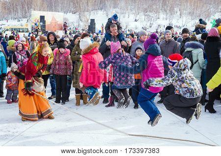 Irkutsk, Russia - February 26, 2016: Shrovetide carnival celebration. Children jumping rope. Traditional Russian folk festival. Off winter