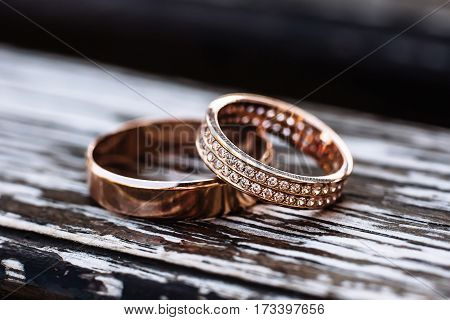 Golden wedding rings on wooden backrgound with small depth of field