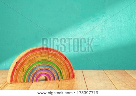 Cartoon styled rainbow on wooden table over grunge bright background. 3d rendering
