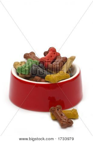 A bright red bowl brimming with bone-shaped dog treats. poster