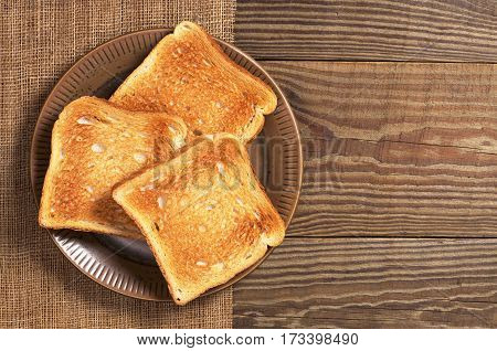 Slices of toasted bread in plate on wooden table top view. Space for text
