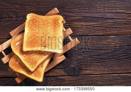 Slices of toasted bread on dark wooden table top view. Space for text