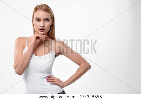 Slim sexy young woman is standing with arm akimbo and posing. She is touching face and looking forward with confidence. Isolated and copy space in right side
