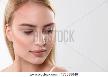 Close up of female face with perfect smooth skin. Shy girl is looking down with pretty smile. Isolated and copy space in right side