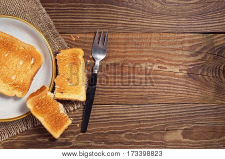 Toasted bread and fork on old wooden table top view. Space for text