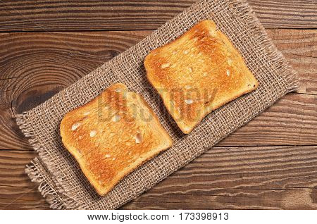 Slices of toasted bread on old wooden table close up top view