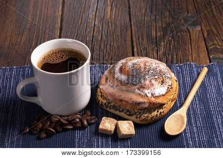 Cup of coffee and delicious bun with poppy seeds on rustic wooden table