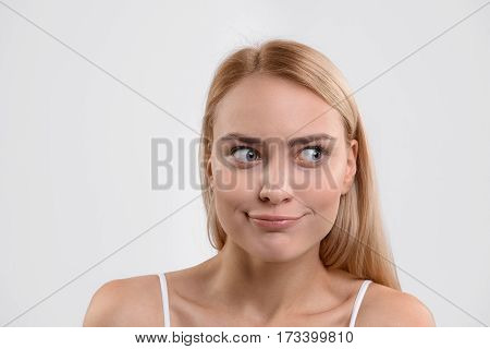 Sly young woman with funny face is looking aside with curiosity. Her lips are folded in strange smile. Isolated