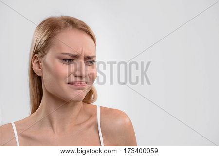 Young woman is standing and looking aside with disgust. Isolated and copy space in right side
