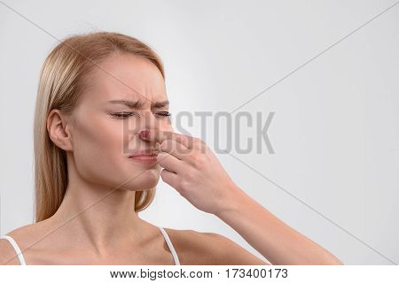 What a terrible smell. Disappointed girl is pinching her nose by fingers with aversion. Her eyes are closed. Isolated and copy space in right side