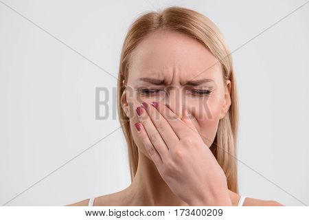 Frustrated young woman is closing her nose with disgust. Isolated and copy space in left side