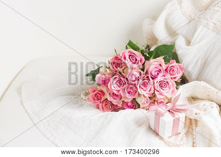 Female dress and jewellery with freah roses bouquet and gift box on chair with copy space