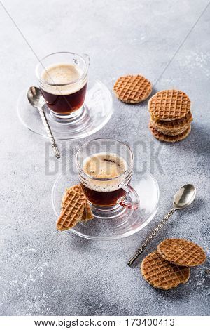 Glass cups of coffee with mini stroopwafel, syrupwaffles cookies on light gray background with copy space.