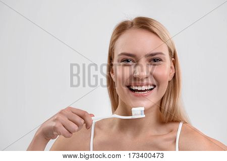 I always brush my teeth. Happy young woman is standing and holding toothbrush with paste. She is looking at camera and smiling. Isolated