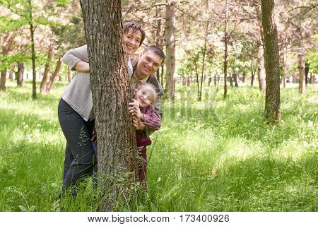 Happy family and child in summer park. People hiding and playing behind a tree. Beautiful landscape with trees and green grass