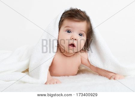 Adorably baby lie on white towel in bed. Happy childhood and healthcare concept