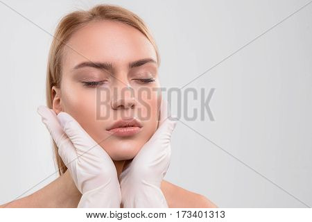 Young skin is perfect. Close up of doctor hands in gloves touching female face. Young woman closed eyes with tranquility. Isolated and copy space in right side