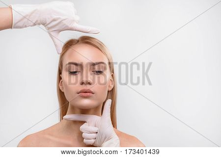 Preparation for plastic surgery. Doctor raising hands to female face while making frame over head by fingers. Isolated and copy space in right side