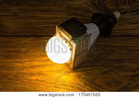 Diy led lamp with huge heatsink with ventillator on it. Ugly and messy fast handmade assembly. High power led with half-spherical diffuser used. Dark flat wooden background with selective focus.