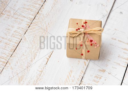 Gift box wrapped in craft paper tied with twine tender small red flower white plank wood background minimalistic copyspace kinfolk top view