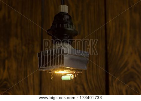 Diy led lamp with huge heatsink on it. Ugly and messy fast handmade assembly. High power led without diffuser used. Dark wooden background with selective focus.