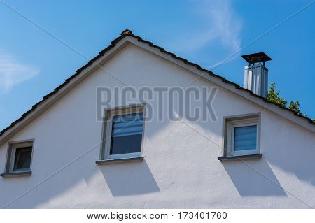 Gable side of a multi-family house of the 60s against blue sky.