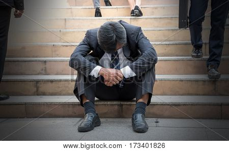 Depressed businessman bending down the head sitting on the stairs. Middle edge man feel frustrated after business failure.