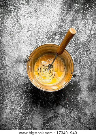 Baking Background. Whisking Fresh Eggs In A Bucket On A Rustic Background.