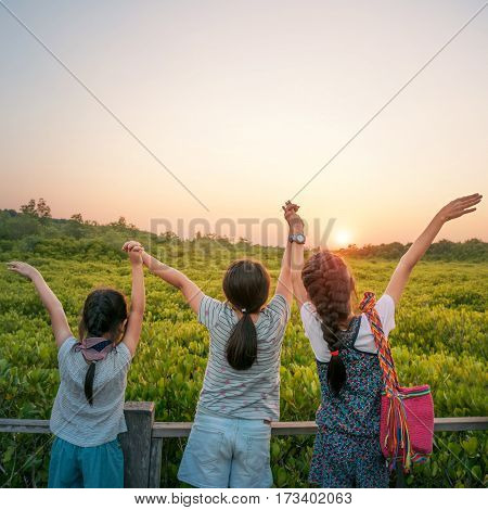 Tree Asian sister young girls holding hands and watching sunset at Tung Prong Thong Golden Mangrove Field Klaeng Thailand.