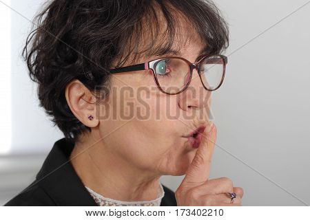 portrait of beautiful mature woman with finger on her lips