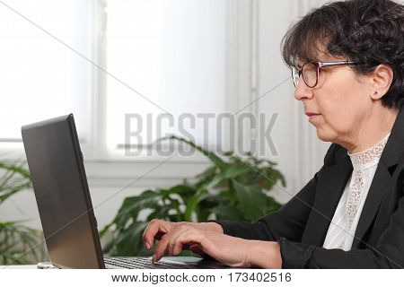 A smiling brunette mature woman using laptop